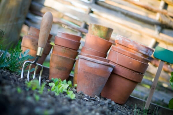 macetas de barro amontonadas con herramientas de huerto